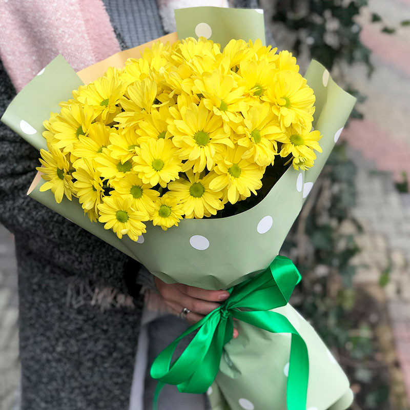 Yellow chrysanthemums in green paper photo